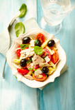 Pasta with tuna, cherry tomatoes, black olives, spices and fresh basil. Home made food. Concept for a tasty and healthy meal. Bright wooden background. Top view.  - 225737000