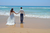 Long-haired brunette bride and groom in a suit. newlyweds holding hands, go to the sand in the water of the Indian Ocean. Wedding and honeymoon in the tropics on the island of Sri Lanka - 225746250