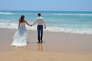 Long-haired brunette bride and groom in a suit. newlyweds holding hands, go to the sand in the water of the Indian Ocean. Wedding and honeymoon in the tropics on the island of Sri Lanka