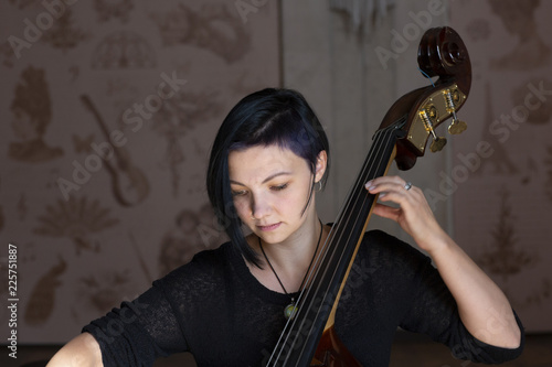 Young positive brunette playing double bass - 225751887