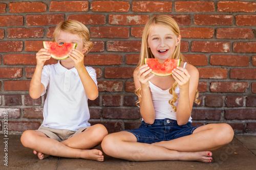 Foto Murales Cute Young Cuacasian Boy and Girl Eating Watermelon Against Brick Wall