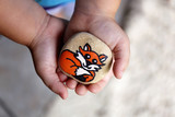Young Child's Hands Holding a Painted Rock with A Cartoon Fox on It