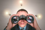 Businessman with binoculars is looking for new business ideas.