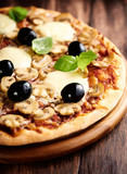 Pizza with mozzarella, mushrooms, black olives and fresh basil. Italian pizza. Homemade food. Symbolic image. Concept for a tasty and hearty meal. Rustic wooden background. Selective focus. Close up.  - 225809699