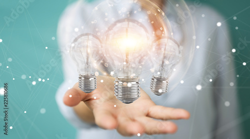 Leinwanddruck Bild Businesswoman connecting modern lightbulbs with connections 3D rendering
