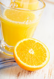 Halved orange and orange juice. Concept for healthy nutrition. White wooden background. Close up.  - 225821000