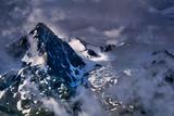 ośnieżone szczyty alpejskie w chmurach i mgłach