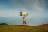 Indian man carrying a bag of harvested crops