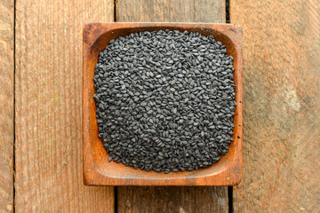 Black sesame seeds in a wooden dish