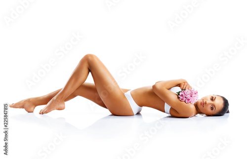 Leinwanddruck Bild Young woman with beautiful long legs. Photo of tanned woman's body isolated on white background. Beauty & Skin care concept.