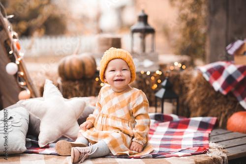 Leinwandbild Motiv Stylish baby girl 1-2 year old wearing autumn clothes posing with pumpkins outdoors. Childhood. Fall season. Thanksgiving.