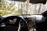 view of sunny forest from car interior with steering wheel