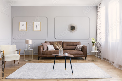 Leinwandbild Motiv Minimal interior design of living room with brown leather couch, retro armchair coffee table and golden decorations, real photo