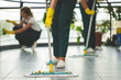 Quadro Close-up on cleaning specialist with yellow gloves holding mop while wiping floor