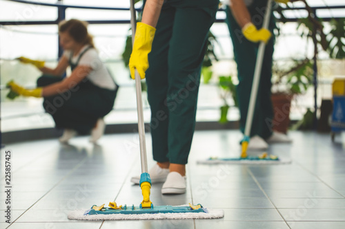 Foto Murales Close-up on cleaning specialist with yellow gloves holding mop while wiping floor