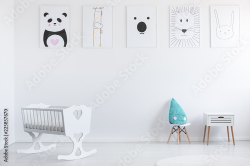 Leinwandbild Motiv Posters on white wall in minimal kid's room interior with cradle and blue pillow on stool. Real photo