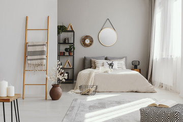 Mirror and clock above bed in bright bedroom interior with pouf and flowers next to ladder. Real photo