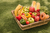 Fresh healthy tropical fruit on a picnic blanket on the grass with grapes, apple, grapefruit, orange and banana - 225861072
