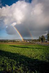 Regenbogen seitlich eines Dorfes