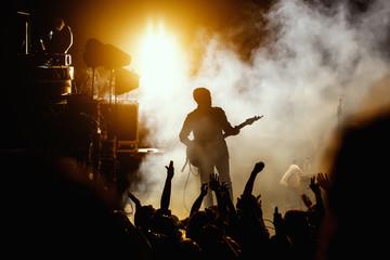 Silhouette of guitar player, guitarist perform on concert stage. Dark background, smoke, concert spotlights.