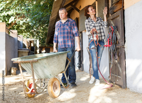 Leinwanddruck Bild Smiling couple with barrow standing at horse stable outdoor