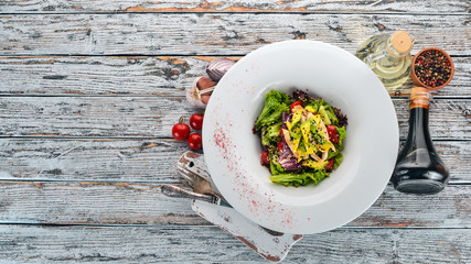 Vegetable salad with chicken fillet and avocado. On a wooden background. Free space for text. Top view.