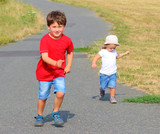 Two kids running together. Children playing and enjoying life during summer  vacations. - 225917665