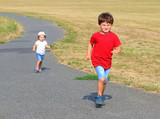 Two kids running together. Children playing and enjoying life during summer  vacations. - 225917666