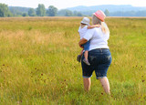 Overweight mother with her child walking together on meadows. Family enjoying life on countryside. - 225917811