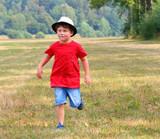 Little boy running on meadows. - 225917878