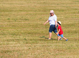 Overweight mother with her child walking together on meadows. Family enjoying life on countryside. - 225917888