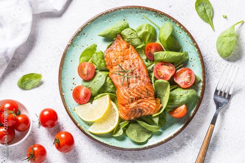 Leinwandbild Motiv Baked salmon fish fillet with fresh salad top view.