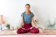 Leinwanddruck Bild - mindfulness, spirituality and healthy lifestyle concept - woman meditating in lotus pose at yoga studio