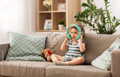 childhood, kids and technology concept - lovely redhead baby girl in headphones listening to music at home - 225926262