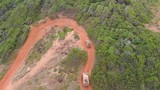 Aerial drone shot following army land rovers, four-wheel driving on a winding red sand road, on a desert, in Cape york, Queensland, Australia - 225937624