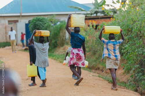 Foto Murales children carrying water cans in Uganda, Africa