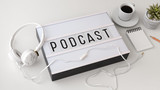 Podcast concept with headphones on white table