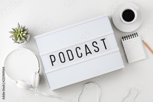 Podcast word on lightbox with headphones on white table - 225969064