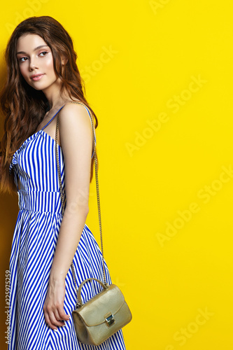 Young woman posing in blue sarafan on a yellow background.