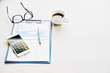Table of financial manager with report, coffee and smartphone with calculator application on it
