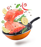 Flying salmon steaks and spices over a frying pan. File contains clipping path. Isolated on a white background. - 225977201