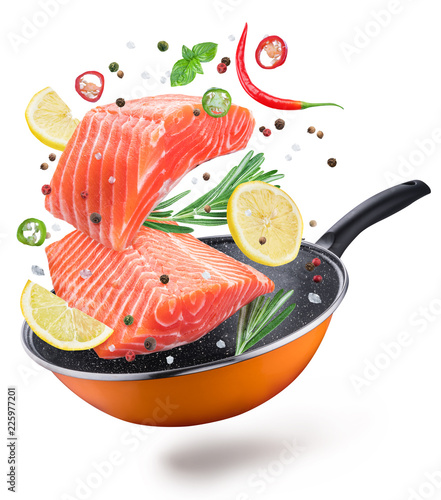 Flying salmon steaks and spices over a frying pan. File contains clipping path. Isolated on a white background.