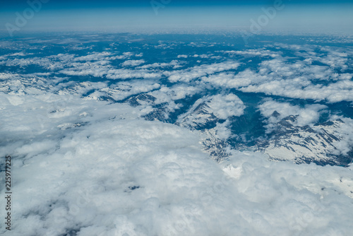 White heavy clouds in the blue sky. Panoramic cloudscape above the clouds. - 225977225