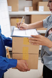 Delivery service manager signing document and taking parcels from courier - 225977456