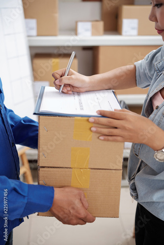 Delivery service manager signing document and taking parcels from courier © DragonImages
