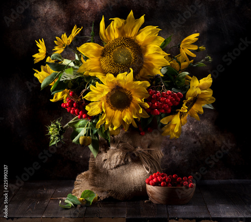 Still life with sunflowers and autumn flowers in a vase on a wooden background © Rozmarina
