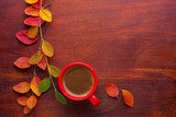 Red cup of coffee and colorful autumn leaves on the wooden table. Top view. - 225998049
