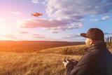 Man with remote controller operating flying drone or quad copter - modern small aircraft for aerial video making