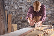 Carpenter smoothing out long wooden beam with tool