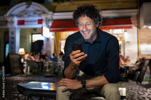 Leinwanddruck Bild Mature happy man using phone at night